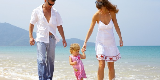 Couple walking along beach with a child